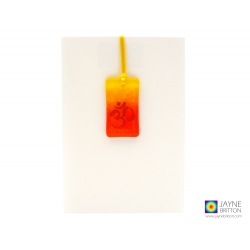 Handmade fused glass orange and yellow light catcher with and Om symbol kiln fired onto the glass. Presented on a plain white greeting card.    Om signifies the basic vibration of the universe. It represents the essential rhythm of energy of which all mat